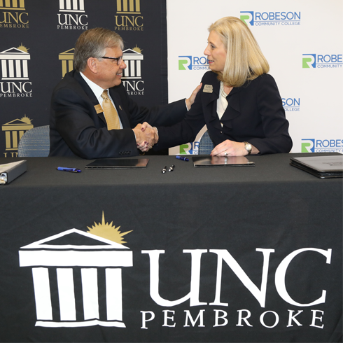 Chancellor Robin Cummings signs the official BraveStep agreement with RCC President Kimberly Gold