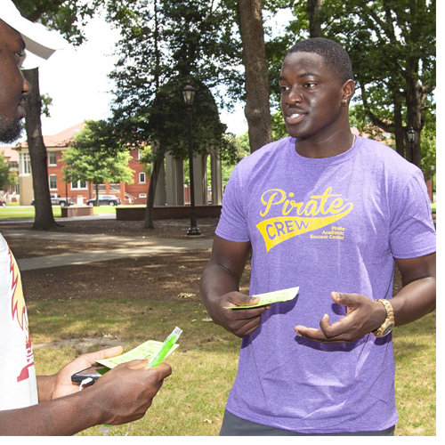 Davarion David, center, and Brittany Hoyt, assistant director at the Pirate Academic Success Center, talk to a summer school student about what the center has to offer while passing out popsicles on the mall Thursday. (Photos by Rhett Butler)