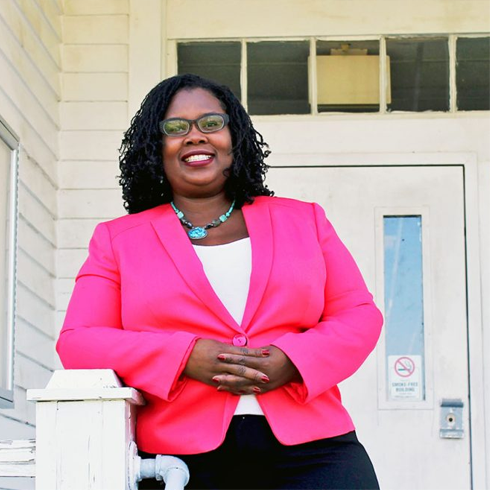 Dr. Melissa Stuckey, ECSU professor of history, stands in front of the Rosenwald School building on campus. ECSU was just awarded a National Endowment for the Humanities grant to help renovate this and the Prinicpal's House for a planned African American American Research and Cultural Heritage Center.