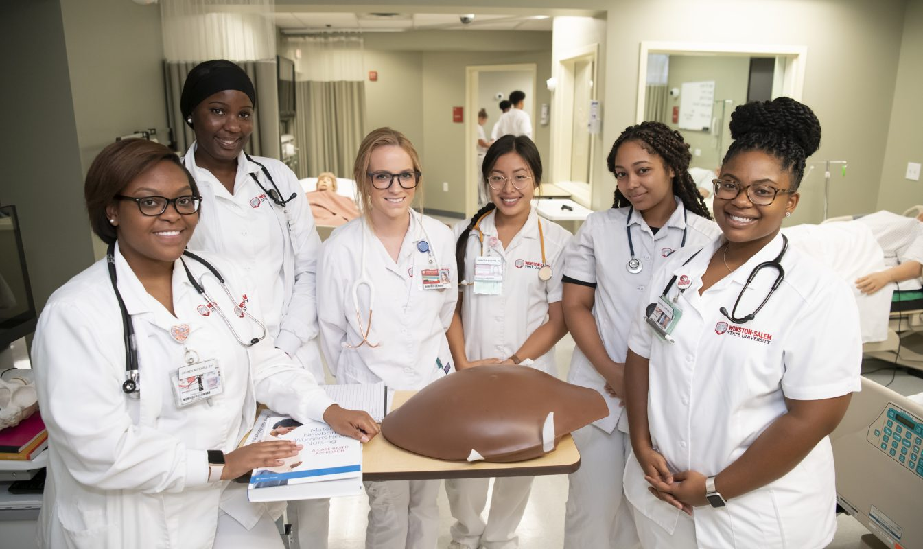 A group of nursing students gather around a model torso.