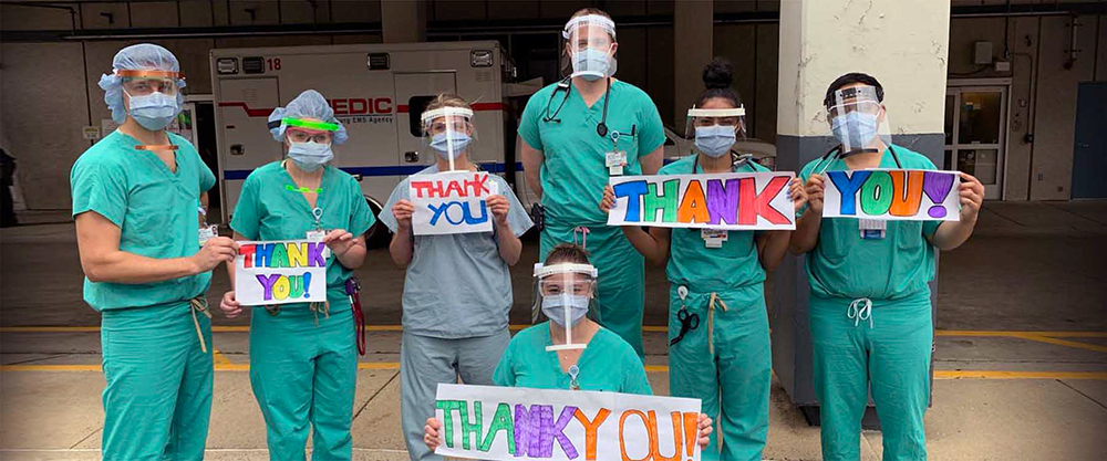 Medical professional hold up a thank you message to UNC Charlotte