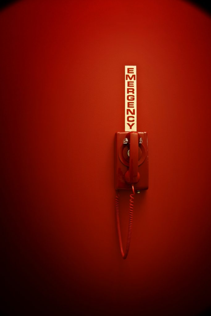 Red telephone with emergency sign.