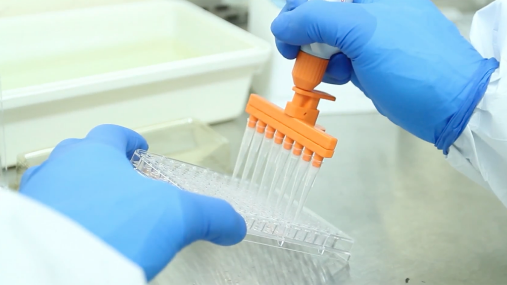 Close-up shot of hands injecting serum into plastic vials