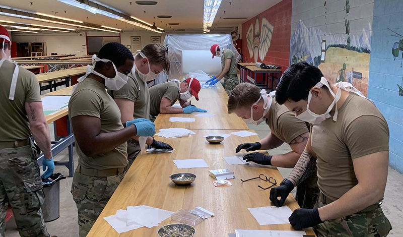 Soldiers stand around workshop tables assembling N95 masks