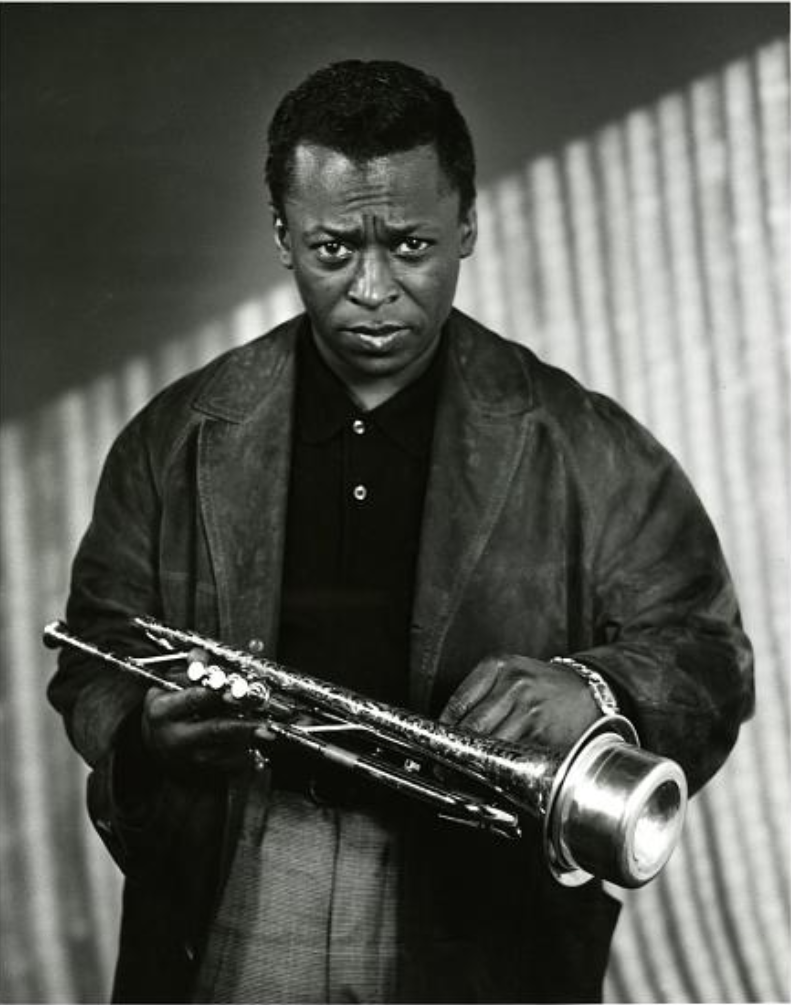 Miles Davis holds a muted trumpet