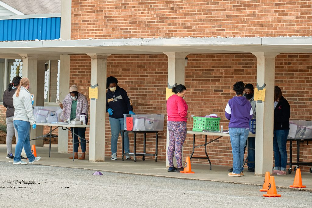 Parents line up outside Moss Street Partnership school; faculty and staff stand behind tables distributing tablets