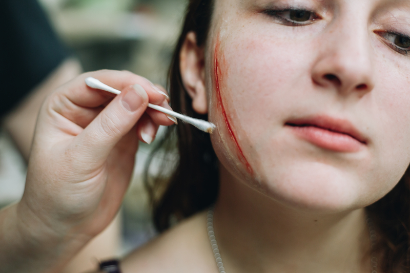 Makeup applied to make a woman's cheek look as if it's been gashed