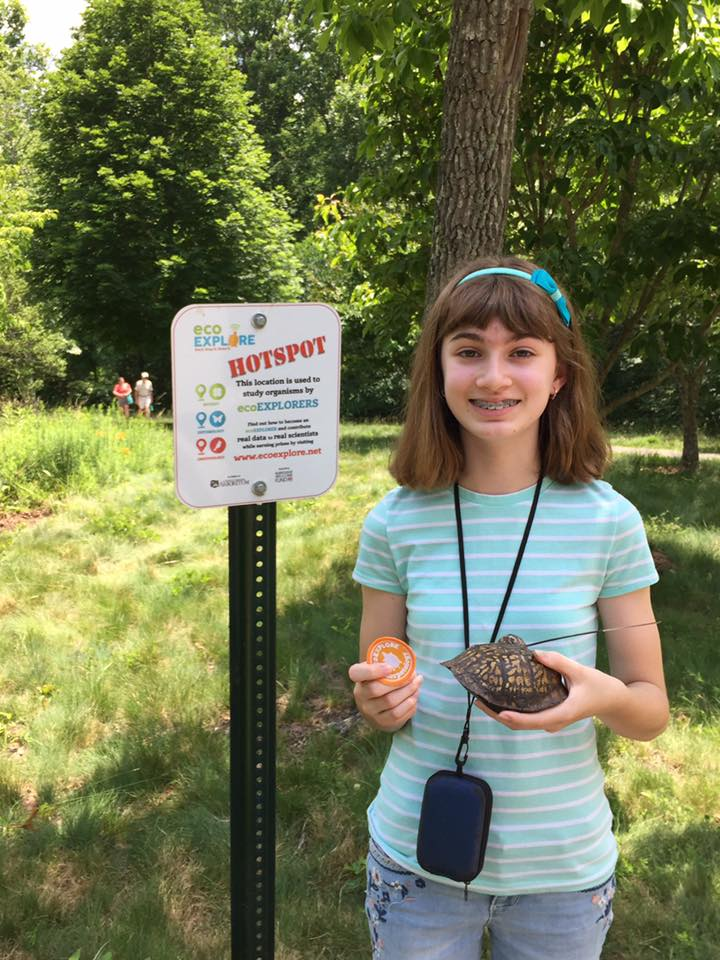 """A girl holds a turtle while standing next to a """"hot spot"""" sign"""