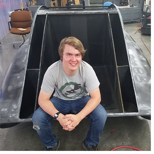 Industrial design major and Raleigh native John Lalevee poses with the unfinished solar vehicle, ROSE, which he helped design during the 2017–18 year. Photo submitted